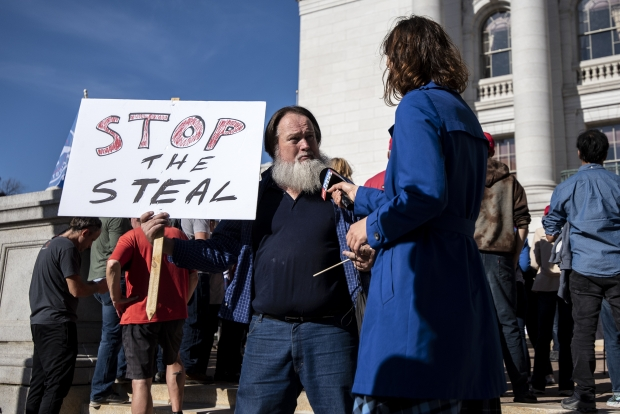 A supporter of President Donald Trump holds a sign as he speaks to a reporter Saturday, Nov. 7, 2020, in front of the Wisconsin state Capitol. Angela Major/WPR