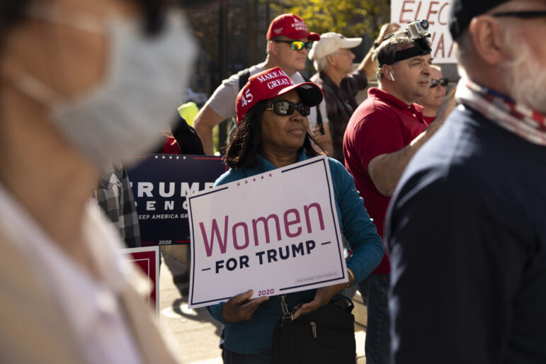"""Marie, center, from Pleasant Prairie, Wis., rallies in support of President Donald Trump at the Wisconsin State Capitol in Madison, Wis., on Nov. 7, 2020. Earlier in the day major media organizations called the presidential election in favor of Joe Biden, the Democratic candidate. """"I saw some of the fraud with my own eyes,"""" she said, echoing Trump's false claims that voter fraud tilted vote counts in Biden's favor. Marie, who declined to give her last name, said she is a lifelong Republican. Coburn Dukehart / Wisconsin Watch"""