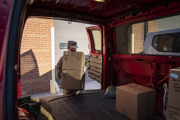 A member of the Wisconsin National Guard loads boxes of PPE into a van Monday, Dec. 21, 2020, outside of a warehouse in Madison. Angela Major/WPR