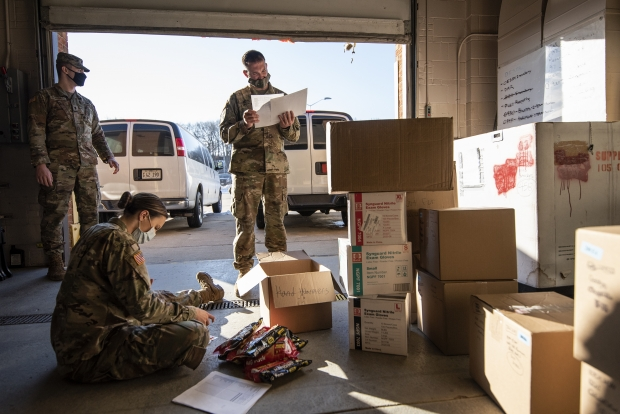 Members of the Wisconsin National Guard load boxes with hand warmers and PPE on Monday, Dec. 21, 2020, before distributing them to COVID-19 testing sites across the state. Angela Major/WPR
