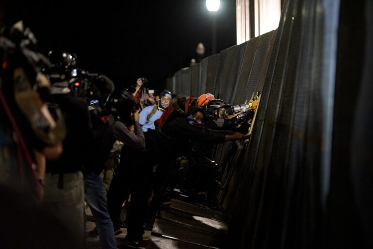 Protesters attempt to push down a fence in front of the Kenosha County courthouse on Aug. 25, 2020, in Kenosha, Wis. The city faced consecutive days of unrest after Kenosha Police officer Rusten Sheskey shot Jacob Blake seven times in the back after police responded to a domestic dispute. Angela Major / WPR