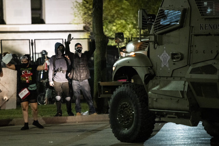 Protesters stand in front of an armored Kenosha County Bearcat vehicle as officers attempt to disperse the crowd Aug. 25, 2020, in Kenosha, Wis. The city faced consecutive days of unrest after Kenosha Police officer Rusten Sheskey shot Jacob Blake seven times in the back after responding to a domestic dispute. Law enforcement's response in Kenosha — including the early use of armored vehicles and the decision to arrest protesters en masse for curfew violations — ran counter to established best practices for policing protests, experts say. Angela Major / WPR