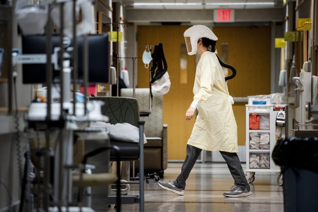 A health care worker in a PAPR hood walks through the hallway inside a COVID-19 unit at UW Health's University Hospital in Madison, Wis., on Nov. 17, 2020. The pandemic has hit Wisconsin and other Midwestern states hard in recent months, causing record levels of infections and death. Angela Major / WPR