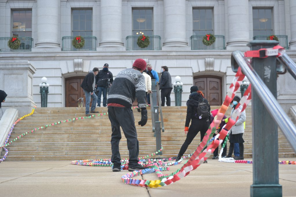 Volunteers array strands of an 833-foot paper chain on the steps of the state Capitol Wednesday, commemorating Wisconsin residents who died from COVID-19. Photo by Erik Gunn/Wisconsin Examiner.