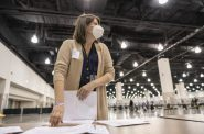 "Claire Woodall-Vogg, executive director of the Milwaukee Election Commission, works at the presidential recount at the Wisconsin Center convention center in Milwaukee on Nov. 25, 2020. Woodall-Vogg says that when faced with the monumental task of running an election, ""When there's no one else to do it, you just … do it."" Sara Stathas for Wisconsin Watch"