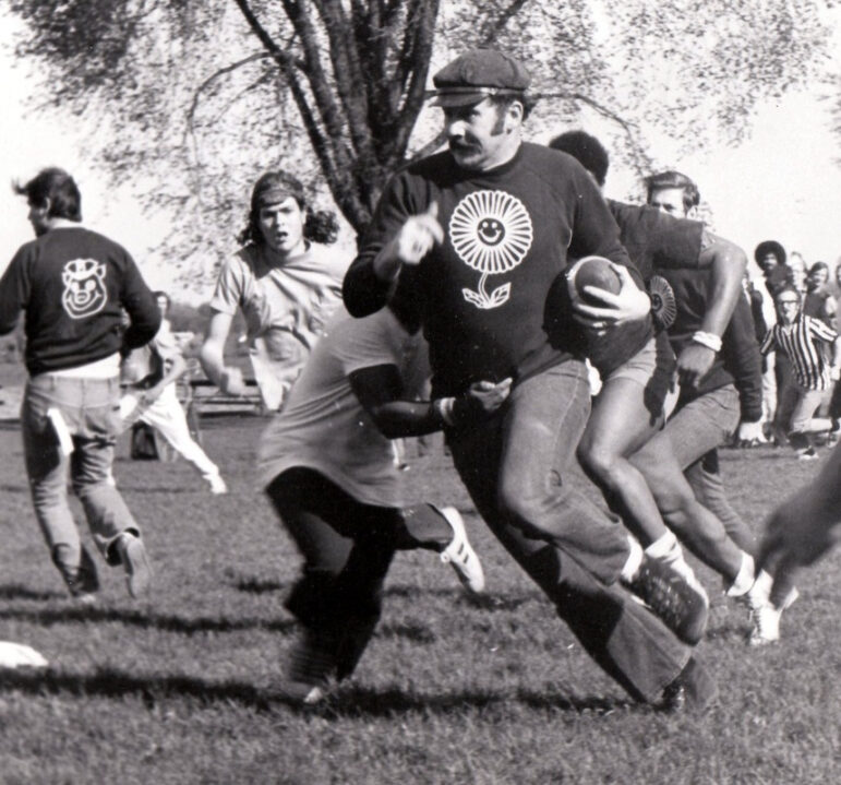 """In his second year as Madison police chief in 1973, David Couper runs an outside sweep during a community-building football game billed as """"Freaks vs. Fuzz."""" It was among many of Couper's efforts to build trust between residents and police officers following clashes in earlier years. Courtesy of David Couper"""