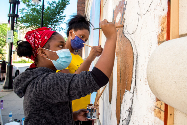 """O'Keeffe Middle School classmates Shahaney Williams, left, and Yasmine Clendening paint a mural on Lake Street in downtown Madison, Wis. on June 11, 2020. """"I thought it was important to show that some people actually care,"""" Williams says, calling the murals an alternative to participating in the protests. """"Some people want to participate, but they're too afraid to walk with (the protesters), because of the tear gas and rubber bullets."""" Will Cioci / Wisconsin Watch"""