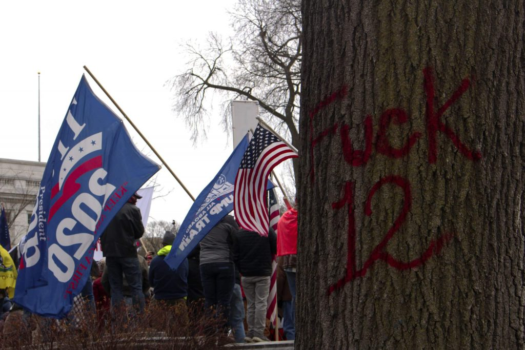 Evidence of Wisconsin's year of political protest with pro-Trump protesters stand near anti-police graffiti from Black Lives Matter protests. Henry Redman/Wisconsin Examiner.