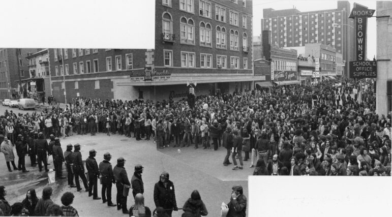 This composite photograph shows an elevated view of an anti-Vietnam War protest at the intersection of Lake and State streets in Madison, Wis. around 1968. A large group of protesters is gathered on State Street, and a line of police officers in riot gear block entry to the University of Wisconsin-Madison campus. Businesses visible include Brown's Books, Rennebohm's, Warner Medlin, Antoine's 5th Avenue, Discount Records and Taco Grande. Wisconsin Historical Society, Image 93540