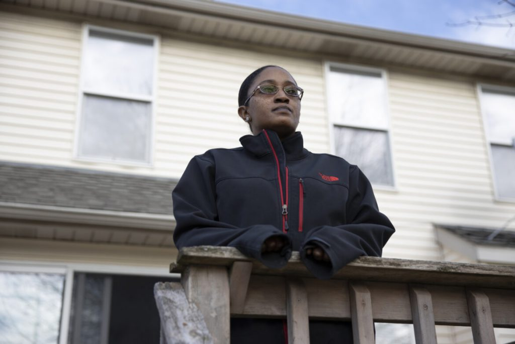 Maneisha Gaston and her son were injured in October of 2020 when another driver blew through a stop sign and crashed into the passenger side of her car before fleeing the scene. Three weeks after receiving treatment for her injuries at Froedtert Hospital in Milwaukee, Gaston learned by certified mail that the hospital filed about $3,300 in liens against her and her son — to potentially cover her bill from the visit, since she lacked health insurance. Gaston is seen here outside her house in Milwaukee on Dec. 21, 2020. Coburn Dukehart / Wisconsin Watch