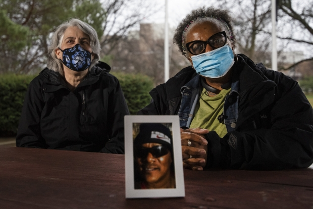 Erin Williams, left, and Dorothy McCollum, right, with a photo of Charles Sheppard, a Navy veteran who helped homeless veterans with his work at the VA. Angela Major/WPR