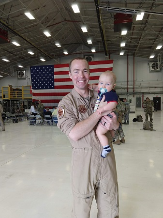 """Capt. Durwood """"Hawk"""" Jones, 37, of Albuquerque, New Mexico, pictured here with his child, lost his life during an F-16 crash in Michigan's Upper Peninsula Dec. 8."""