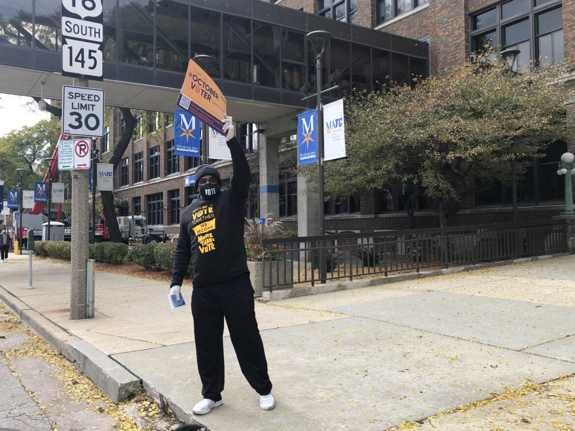 Cy Cullen waves at passersby while volunteering at a When We All Vote event on Oct. 24, 2020. Organizers offered attendees pamphlets on where and how to vote, as well as free food, at the event outside of the Fiserv Forum in Milwaukee. Nora Eckert / Wisconsin Watch