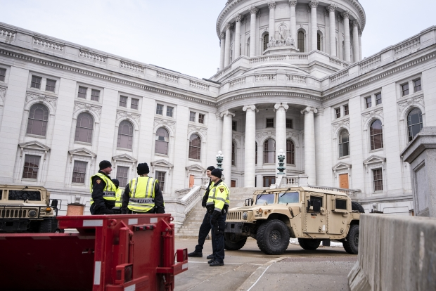 Police gather by a national guard vehicle Sunday, Jan. 17, 2021, at the Wisconsin State Capitol. Angela Major/WPR