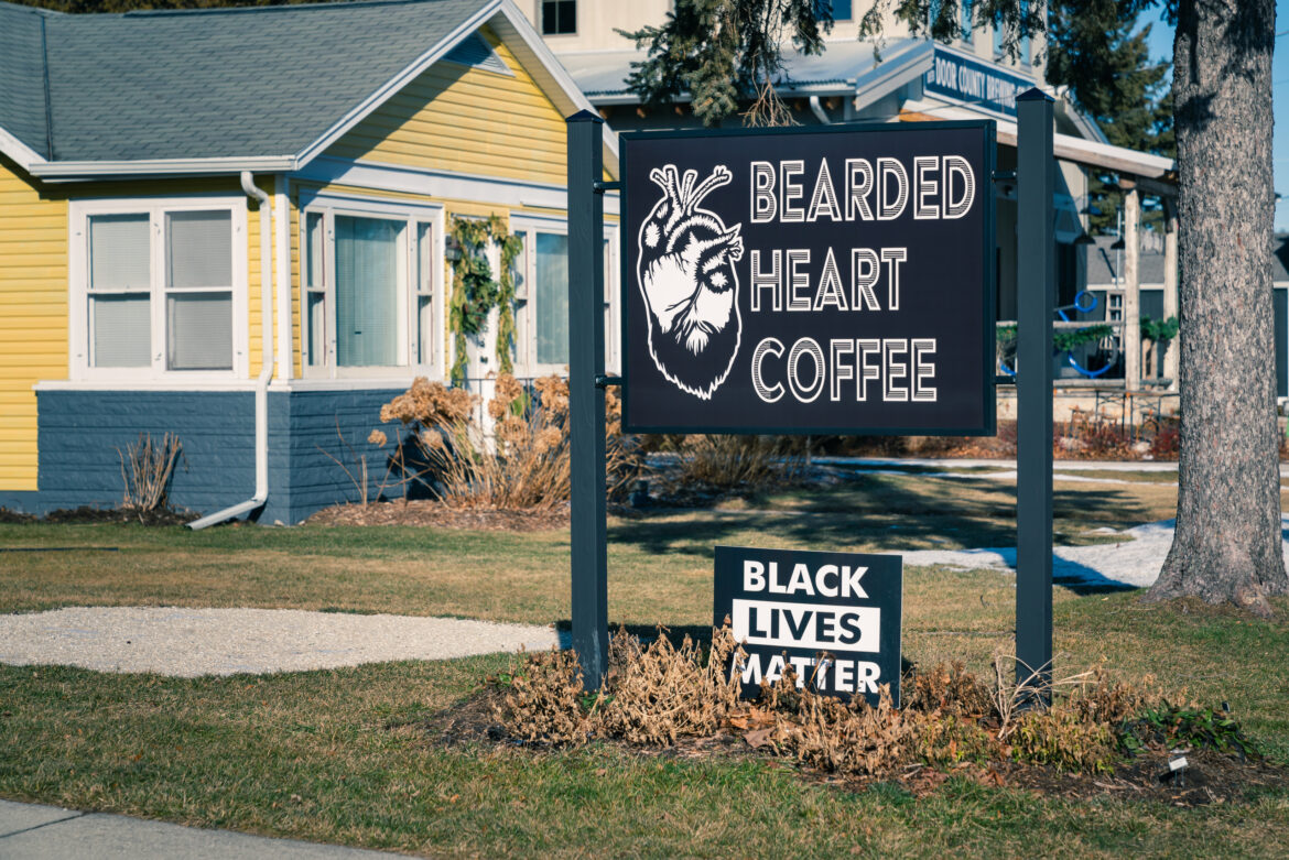 "A ""Black Lives Matter"" sign is shown at Bearded Heart Coffee in Baileys Harbor, Wis. Sage Conrad, the café's manager, says most customers applauded the message, which she posted during a summer of nationwide racial unrest. But several longtime customers left angry voicemails vowing to never return. Another showed up to shout disapproval, Conrad says. Photo taken Jan. 19, 2021. Brett Kosmider for Wisconsin Watch"