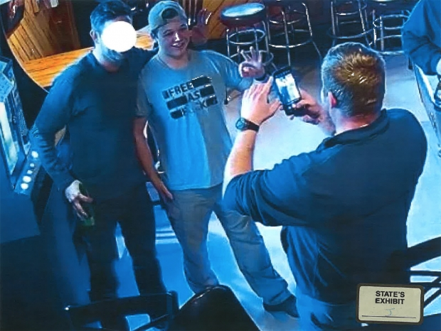 """Kyle Rittenhouse poses for photos at a bar in Mount Pleasant wearing a t-shirt that reads '""""Free as F—-"""" on Jan. 8. Photo from Kenosha County Assistant District Attorney Thomas Binger's motion"""