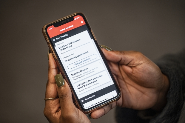 UW-Madison student Kingsley Pissang uses the Safer Badgers phone app to schedule a COVID-19 saliva test on Jan. 14, 2021. During the Spring 2021 semester, students will be required to take two saliva tests per week as part of the Safer Badgers COVID-19 response plan. Bryce Richter/UW-Madison