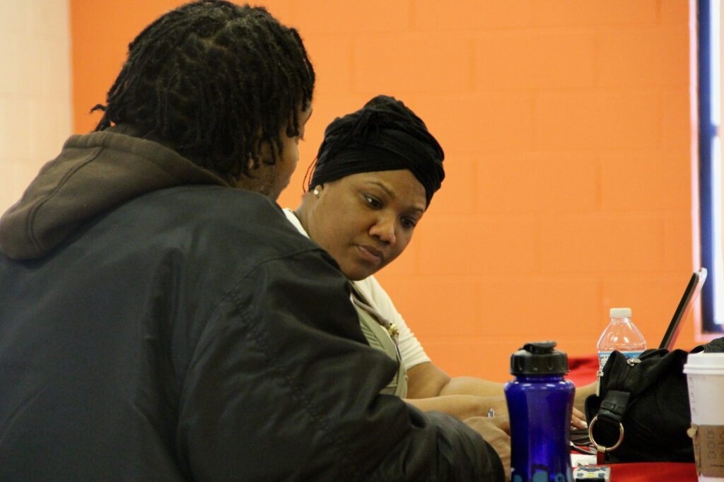 Shanyeill McCloud of Clean Slate Milwaukee checks a man's criminal record to see if he is eligible for expungement during an event in 2016. File photo by Scottie Lee Meyers/NNS.