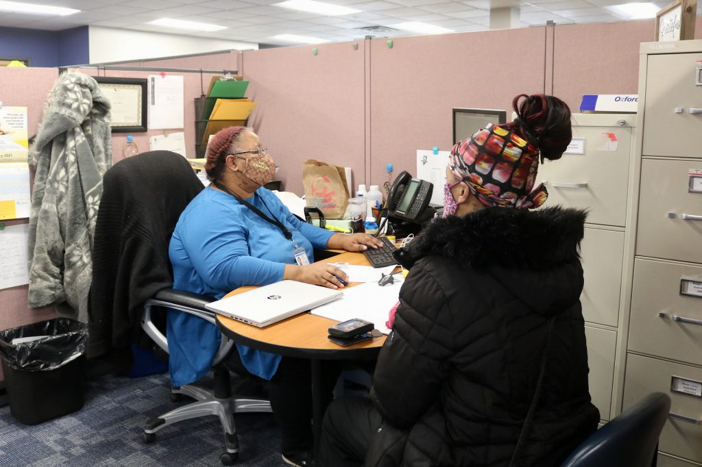Shae Williams (left), a benefit specialist coordinator with the Social Development Commission, helps a client enroll in FoodShare. Photo provided by Kim Dawson-Brooks.