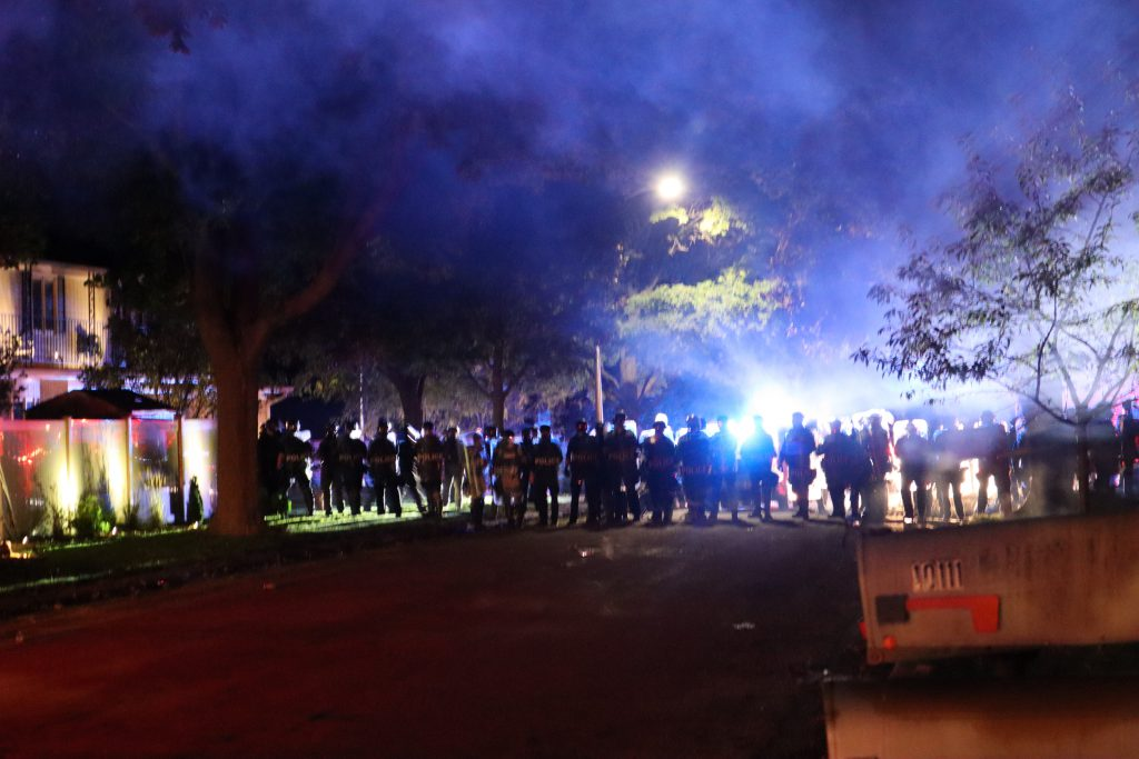 A line of officers in riot and militarized gear block a street in Wauwatosa during the October curfew. Tear gas was still thick in the air. Photo by Isiah Holmes/Wisconsin Examiner.