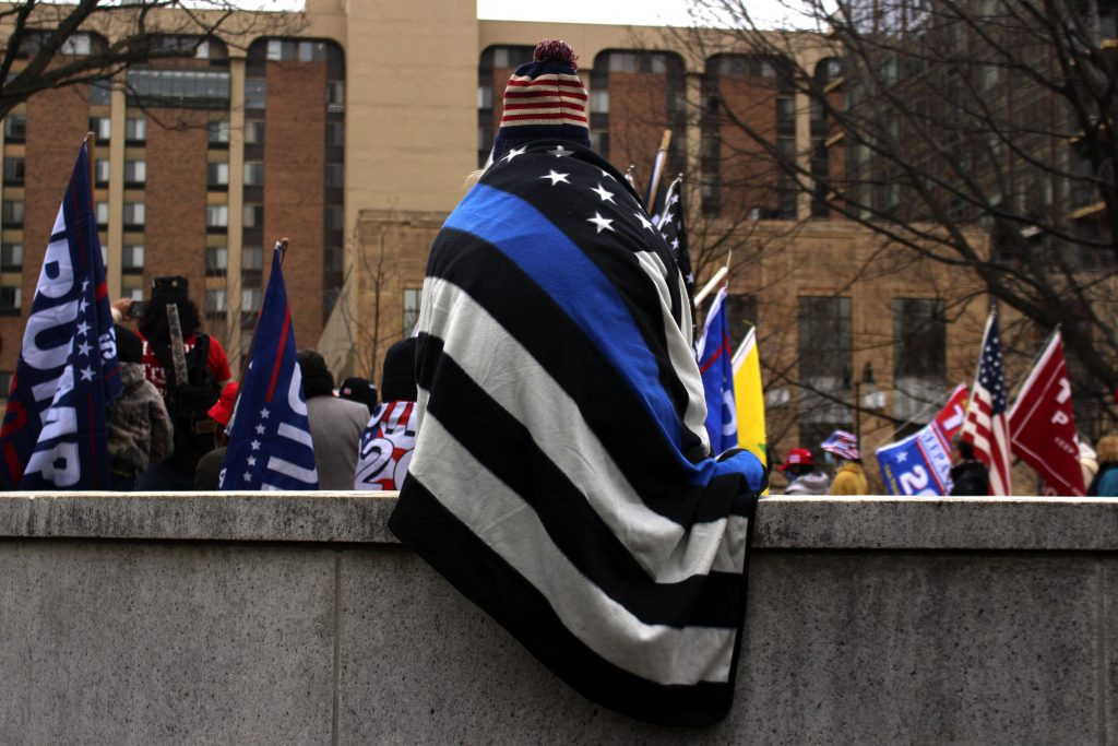 """A rally attendee sits draped in a """"Thin Blue Line"""" pro-police blanket. Photo by Henry Redman/Wisconsin Examiner."""