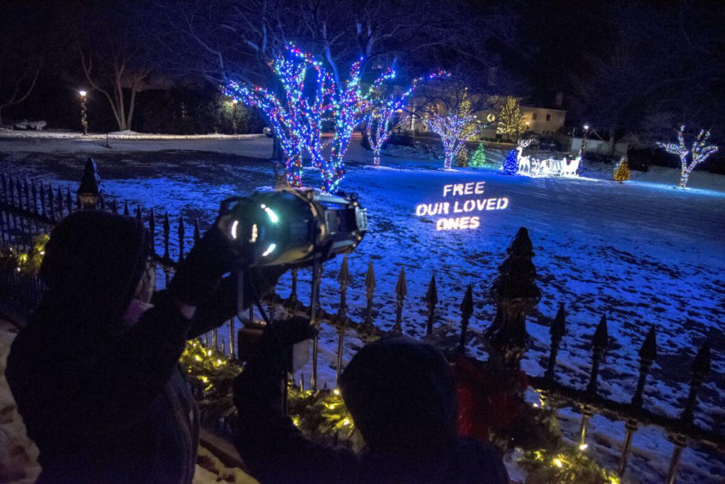 Participants in a candlelight vigil to remember inmates who have died of COVID-19 projected a message onto the front lawn of the Wisconsin governor's mansion in Maple Bluff, Wis. on Dec. 21, 2020. COVID-19 outbreaks in state prisons have killed at least 25 inmates as of Jan. 7, according to the Wisconsin Department of Corrections. Will Cioci / Wisconsin Watch