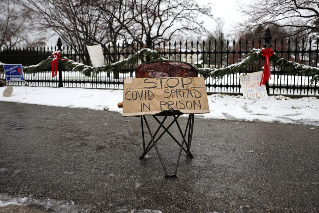 About three dozen people gather outside the Wisconsin governor's mansion in Maple Bluff, Wis., on Nov. 24, 2020. Event organizers sought to draw attention to the thousands of inmates and staff who have contracted COVID-19 in state prisons and called for Gov. Tony Evers to slow the spread of the disease by reducing overcrowding in prisons. Before the pandemic, Evers set a goal to cut the state's prison population in half. But 23 state prisons still exceed their designed capacity. Coburn Dukehart / Wisconsin Watch