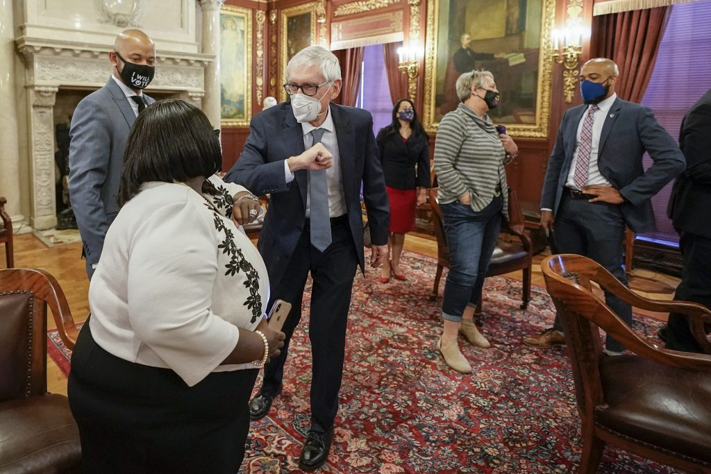 Gov. Tony Evers gives an elbow bump to state Rep. Shelia Stubbs, D-Madison, after Democratic members of Wisconsin's Electoral College cast their votes at the state Capitol in Madison, Wis., on Dec. 14, 2020. Some Republican lawmakers want to award Electoral College votes by congressional district — a proposal that would have given President Donald Trump six of the state's 10 votes. Joe Biden got all of the votes because he won Wisconsin. (Morry Gash/AP Pool)