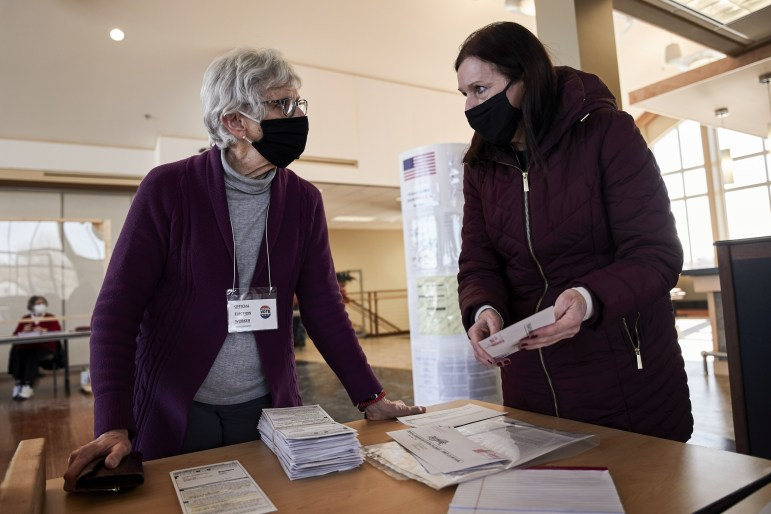 Diane Coenen, Oconomowoc city clerk, drops off absentee ballots to polling station Chief Inspector Arlene Ziety, as she makes her rounds during a primary election on Feb. 16, 2021 in Oconomowoc, Wis. Coenen favors changes to election law to allow clerks to begin processing absentee ballots before Election Day. (Darren Hauck for Wisconsin Watch)