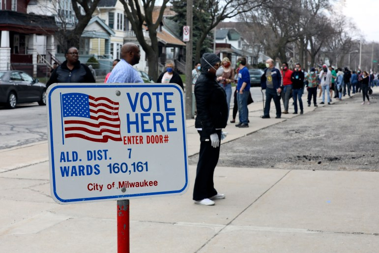 The voting line wraps around the block outside Washington High School in Milwaukee during the primary election on April 7, 2020. Election officials and advocates say the Nov. 3 election was much smoother, with more polling places and few problems reported. (Coburn Dukehart/Wisconsin Watch)