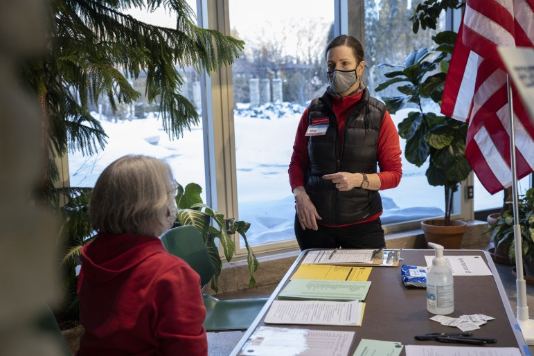 "Poll worker Kathleen Krchnavek, left, talks with chief inspector Meg Hamel at the Olbrich Gardens polling site in Madison, Wis., on Feb. 16, 2021. They were discussing the absentee balloting process. Some Democratic lawmakers in Wisconsin want to make it easier to vote absentee while some Republicans are proposing additional restrictions, which Democrats describe as ""a full-on assault on our elections and the ability for Wisconsinites to vote."" (Credit: Coburn Dukehart / Wisconsin Watch)"