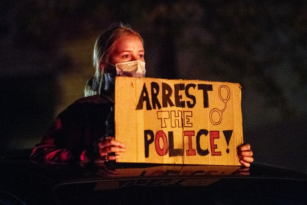 A protester holds a sign as she stands in the open sunroof of a vehicle Wednesday, Oct. 7, 2020, near Wauwatosa. Angela Major/WPR