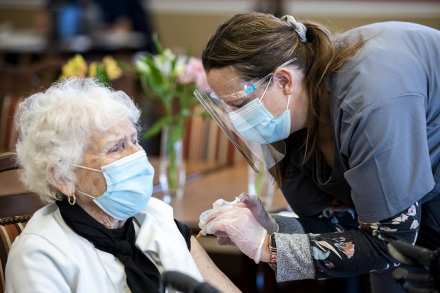 Pharmacist Nicole Hiltunen, right, gives a Touchmark resident the first dose of a COVID-19 vaccine Wednesday, Feb. 3, 2021, in Appleton, Wis. Angela Major/WPR