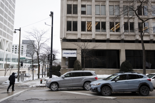 A pedestrian crosses the street in front of the building that was supposed to house the Foxconn North American headquarters Thursday, Feb. 18, 2021, in downtown Milwaukee, Wis. Angela Major/WPR