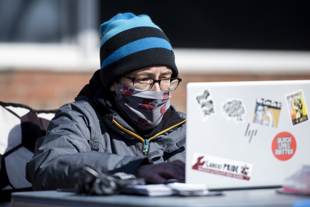 Kate Schultz, an English teacher at La Follette High School, speaks to students virtually outside of the school building Thursday, March 4, 2021, in Madison, Wis. The purpose of this outdoor demonstration was to raise concerns about starting in-person instruction without getting vaccinated for COVID-19. Angela Major/WPR
