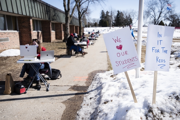 La Follette High School teachers teach their students virtually outside the school building to protest a lack of COVID-19 vaccines for teachers Thursday, March 4, 2021, in Madison, Wis. Angela Major/WPR