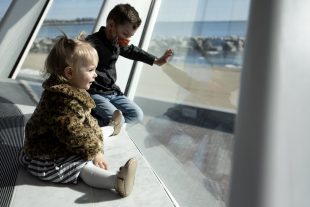 Sullivan, 5, and Violet, 1, look through the glass at the Milwaukee Art Museum to see pedestrians and Lake Michigan on Friday, March 5, 2021, while visiting the museum with their mother, Ashley Stangel of Pewaukee, Wis. Angela Major/WPR