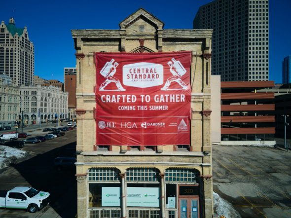 """As seen from I-794, Central Standard Craft Distillery raises a """"Coming Soon"""" banner to celebrate the planned July 22 grand opening of the distillery's downtown Milwaukee experience. Photo courtesy of Central Standard."""