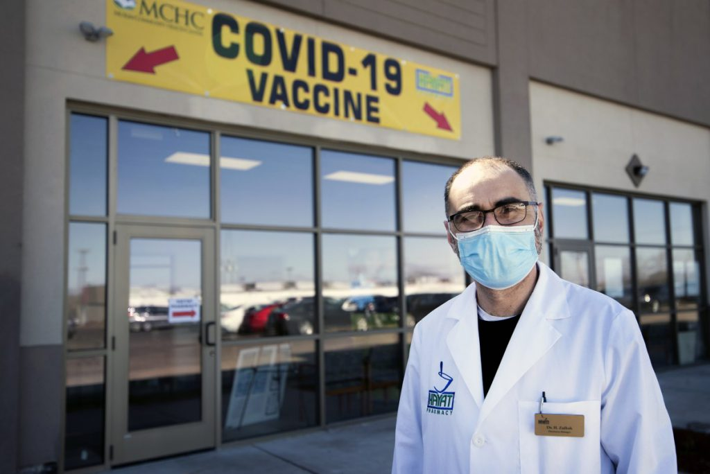 Hashim Zaibak, a founder and pharmacist at Hayat Pharmacy in Milwaukee, stands outside of his business on March 11, 2021. The pharmacy offers walk-in hours for COVID-19 vaccine seekers — an effort to bolster access to those who might otherwise run into technological or language barriers when trying to schedule appointments. Angela Major / WPR