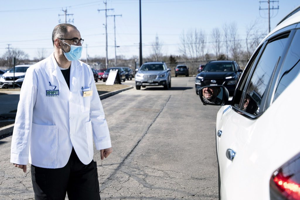 """Pharmacist Hashim Zaibak speaks to a client arriving for a COVID-19 vaccine at Hayat Pharmacy on March 11, 2021. The Milwaukee pharmacy accepts walk-ins who might otherwise struggle to book appointments online. """"We've had slow days when we just vaccinated 50 or 60 people, and we've had some really, really busy days that we were getting close to 1,000 a day,"""" Zaibak says. Angela Major / WPR"""
