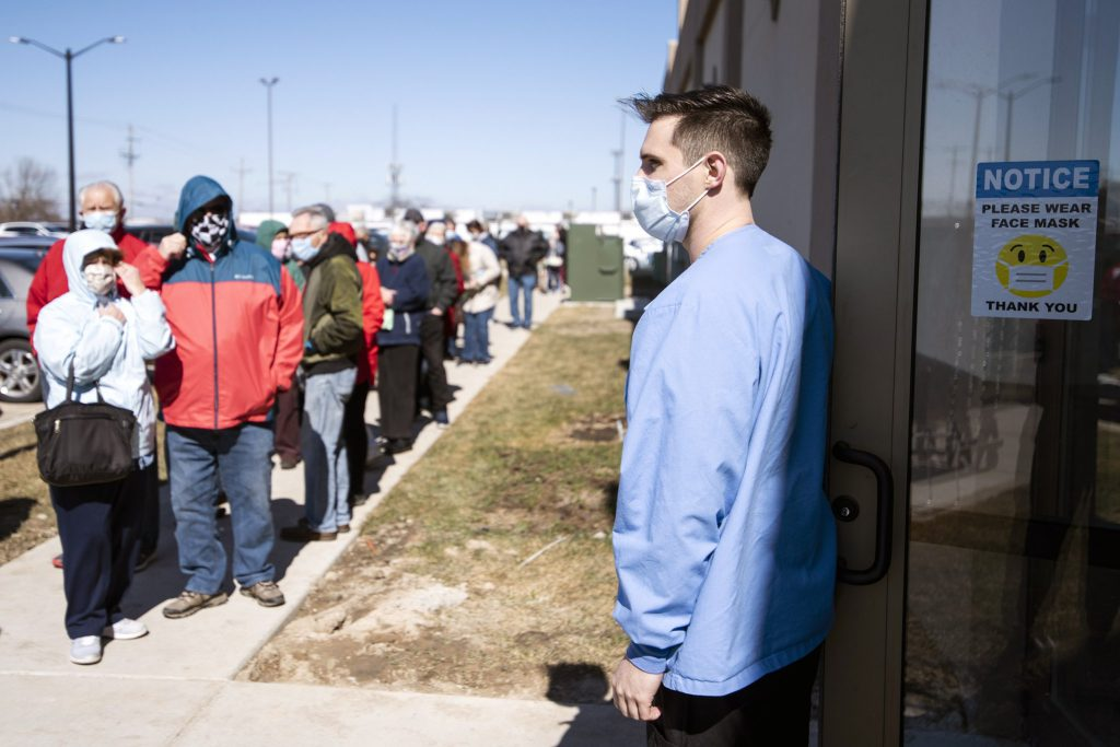 COVID-19 vaccine seekers wait outside of Milwaukee's Hayat Pharmacy on March 11, 2021. Wisconsin is among the nation's leaders in distributing COVID-19 inoculations to those who want them, but demand still outpaces supply, and some eligible residents have struggled to find appointments. The Wisconsin Department of Health Services says it expects to expand vaccine eligibility to all residents ages 16 and older by May. Angela Major / WPR
