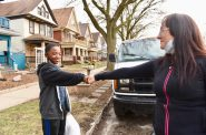 """Laura Manriquez, known to her neighbors as """"Milwaukee's Food Fairy,"""" frequently delivers food from food pantries and stores to those with transportation issues. Here, she fist bumps DelMonte, her Lincoln Village neighbor and mentee. Photo by Sue Vliet/NNS."""