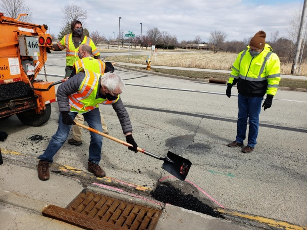 Gov. Tony Evers (foreground) fills potholes during a recent series of events in northern Wisconsin designed to highlight his administration's commitment to funding road repairs in the state. Photo courtesy of Gov. Tony Evers' office.