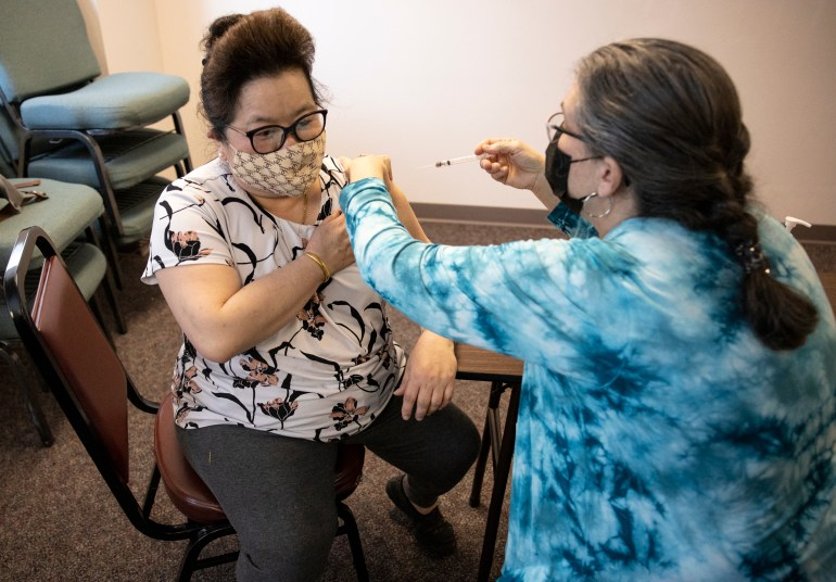 Madison resident Chia Yang, 56, gets her first dose of the Moderna vaccine at a clinic put on by The Hmong Institute, in Madison, Wis., on March 9, 2021. Asian-American families in Wisconsin and nationally are more likely to live in multigenerational households, which are more at risk of contracting COVID-19. Credit: Coburn Dukehart / Wisconsin Watch