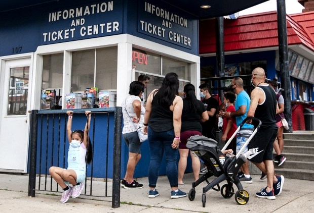 7-year-old Hayley Contreras, left, wears a mask as she hangs on a rail as her family gets tickets for a boat tour Monday, Aug. 10, 2020, in the Wisconsin Dells. Angela Major/WPR