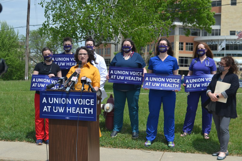 Sen. Melissa Agard speaks Thursday at a news conference promoting legislation she and Rep. Lisa Subeck, far right, plan to introduce that would restore collective bargaining rights at UW Health. Nurses and their supporters in the health care system stand behind. Photo by Erik Gunn/Wisconsin Examiner.