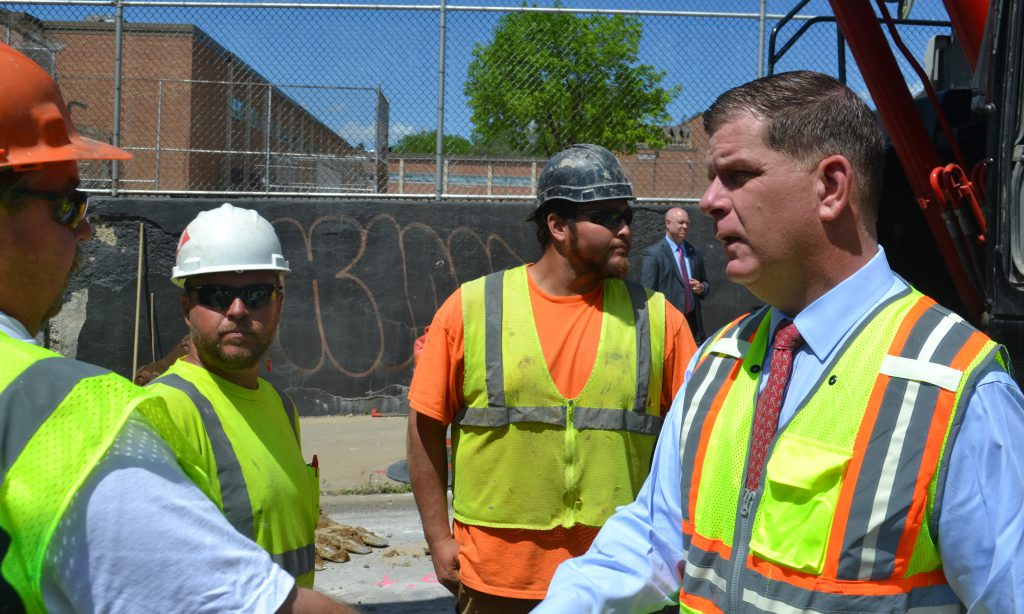 U.S. Labor Secretary Marty Walsh, right, shakes hands with workers on the job site of a Milwaukee Water Works project to replace aging water pipe. Walsh was in Milwaukee on Wednesday to promote the Biden administration's American Jobs Plan and American Family Plan legislative packages. Photo by Erik Gunn/Wisconsin Examiner.