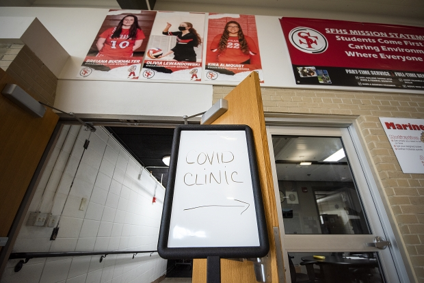 A sign directs high schoolers and community members to the COVID-19 vaccination clinic set up in the school's theater Tuesday, May 4, 2021, at St. Francis High School in St. Francis, Wis. Angela Major/WPR