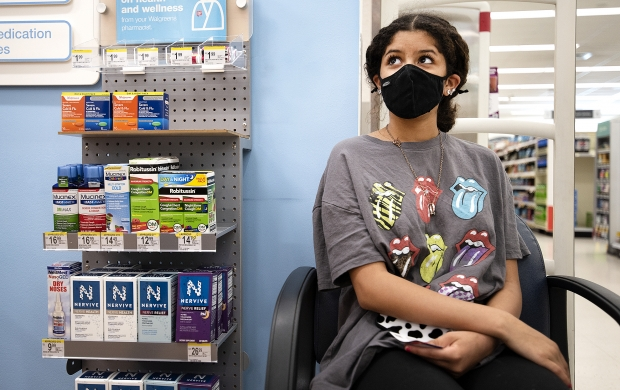 Lily Rodriguez, a 14-year-old, waits in a chair at the Walgreens pharmacy before receiving a COVID-19 vaccine Thursday, May 13, 2021, in Fort Atkinson, Wis. Angela Major/WPR