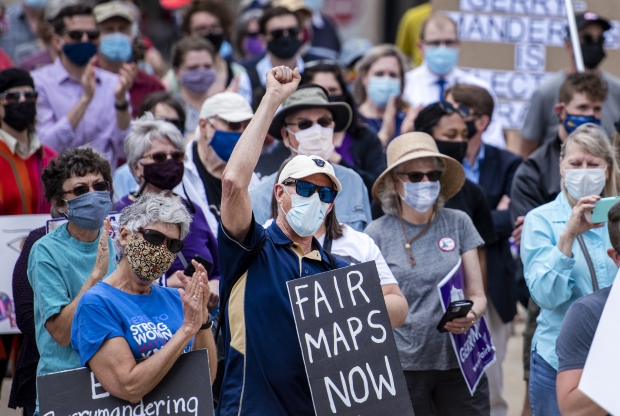 Attendees hold signs at the Rally for Fair Maps on Monday, May 17, 2021, in Madison, Wis. Angela Major/WPR